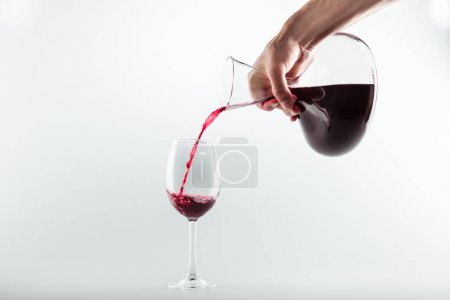 Photo for Cropped shot of person holding decanter and pouring red wine into glass isolated on white - Royalty Free Image