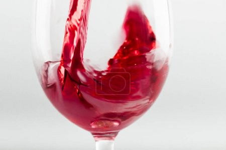 Photo for Close-up view of red wine pouring in glass isolated on white - Royalty Free Image
