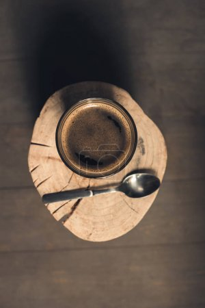 Glass of coffee and spoon on wood
