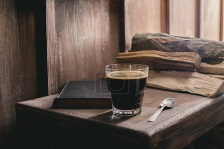 Photo for Glass of coffee drink, old book and spoon on rustic wooden table near pile of firewood - Royalty Free Image