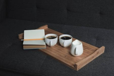 coffee, jug of milk and notebook on tray