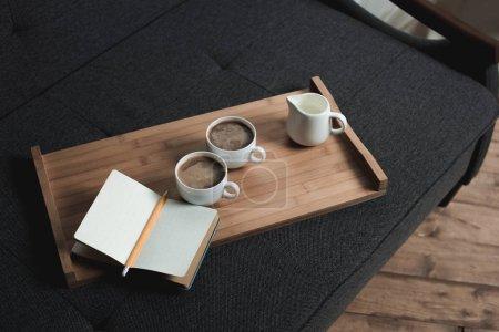 Kaffee, Milchkrug und Notizbuch auf Tablett