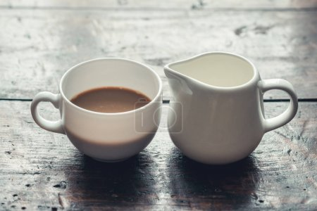 Cup of coffee with milk and jug