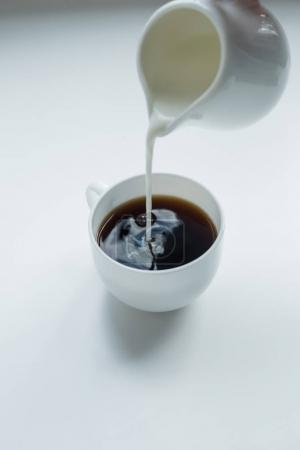Pouring milk into cup of black coffee
