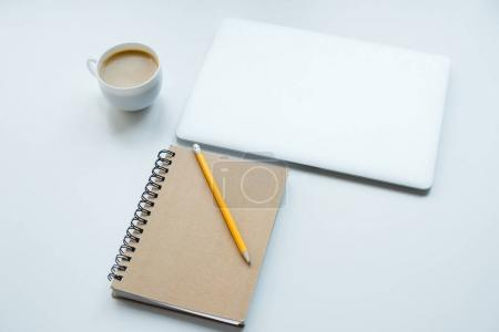 Photo for Laptop computer, notepad with pencil and cup of coffee isolated on white - Royalty Free Image