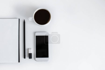 Notepad and smartphone with blank screen