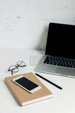 Photo pour Ordinateur portable avec écran blanc, smartphone et bloc-notes sur table blanc - image libre de droit