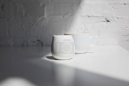 Photo for Cup of coffee and milk jar on white table with sunlight - Royalty Free Image
