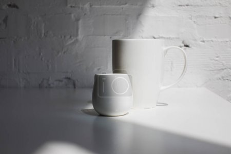 Photo for Big cup of coffee and milk jar on white table with sunlight - Royalty Free Image