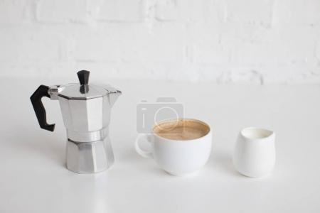 Photo for French press, cup of coffee and milk jar standing in row on white table - Royalty Free Image