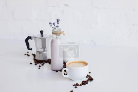 Photo for French press, cup of coffee, milk jar and lavender drink with scattered coffee beans on white table - Royalty Free Image