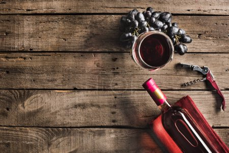 Photo for Top view of bottle of pink wine, corkscrew, wineglass and grapes on wooden tabletop with copy space - Royalty Free Image