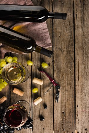 Photo for Top view of two bottles of wine, corkscrew, wineglasses and grapes on wooden tabletop with copy space - Royalty Free Image