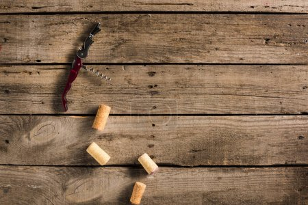 Corkscrew and corks on wooden tabletop