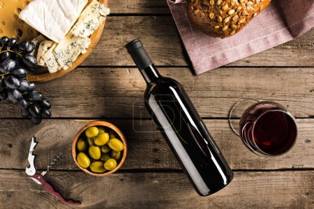 Photo for Top view of bottle of red wine, corkscrew, wineglass, green olives, different cheese and bread on napkin on wooden tabletop - Royalty Free Image