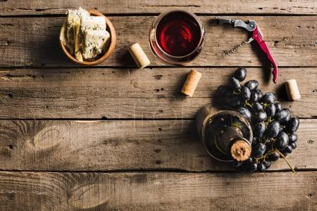 Photo for Top view of bottle of pink wine, corkscrew, wineglass, cheese in bowl and grapes on wooden tabletop with copy space - Royalty Free Image