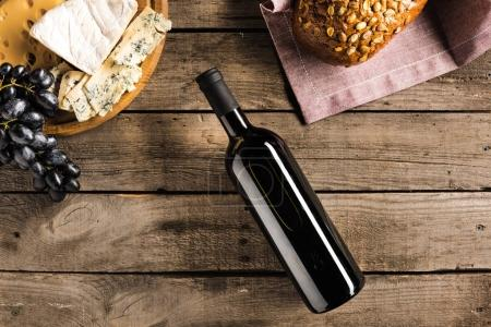 Photo for Top view of bottle of red wine, different cheese and bread on napkin on wooden tabletop - Royalty Free Image