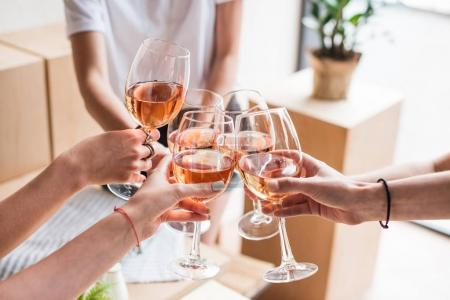 Photo for Cropped view of women clinking with wineglasses with pink wine - Royalty Free Image