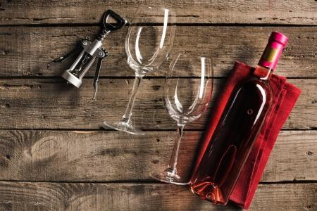 Photo for Top view of bottle of pink wine on napkin, corkscrew and two empty wineglasses on wooden tabletop - Royalty Free Image
