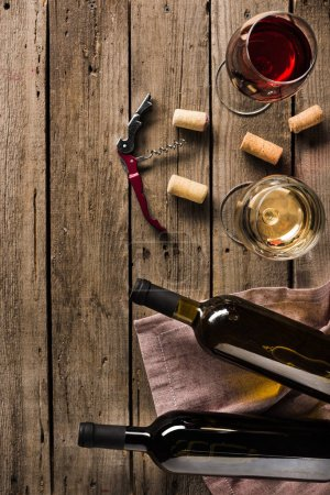 Photo for Top view of two bottles of wine, corkscrew and wineglasses on wooden tabletop with copy space - Royalty Free Image