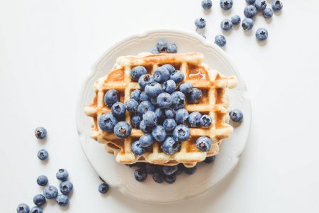 Photo for Top view of plate of tasty stacked waffles with blueberries - Royalty Free Image