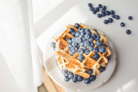 Photo for Plate of tasty fresh waffles with blueberries under sun rays - Royalty Free Image