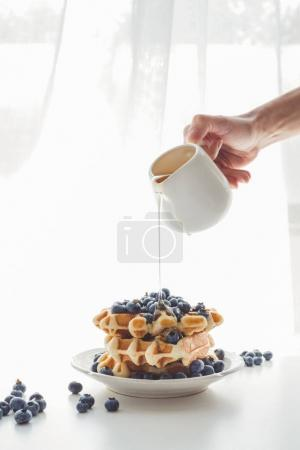 woman pouring honey on tasty waffles