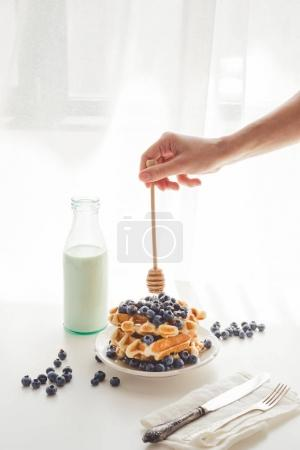 Photo for Cropped shot of woman pouring honey from spoon on tasty waffles - Royalty Free Image