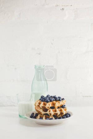 Photo for Delicious breakfast of waffles with blueberries and glass of milk - Royalty Free Image