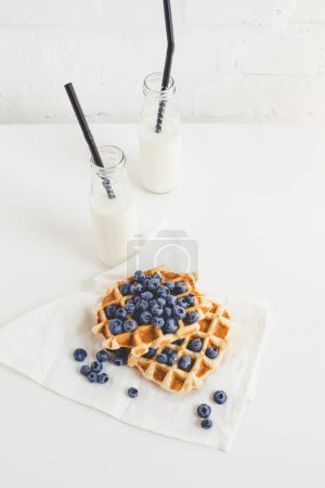 Photo for Delicious breakfast of waffles with blueberries and milk bottles with straws - Royalty Free Image