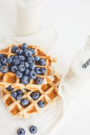 Photo for Delicious breakfast of waffles with blueberries and two bottles of milk - Royalty Free Image