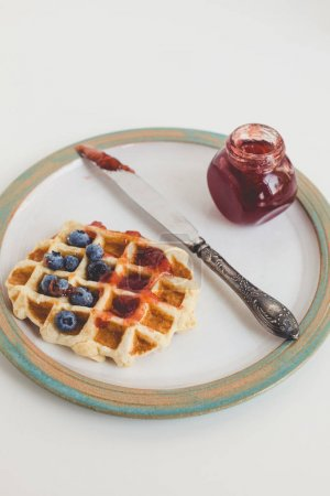 Photo for Tasty waffle with jam, blueberries and knife on vintage plate - Royalty Free Image