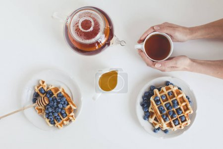 Photo for Top view of delicious breakfast of tasty waffles and tea - Royalty Free Image