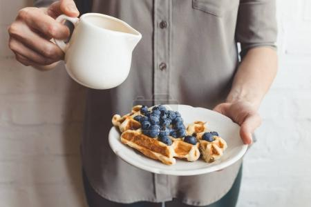 Photo for Cropped shot of woman pouring syrup on tasty waffles - Royalty Free Image