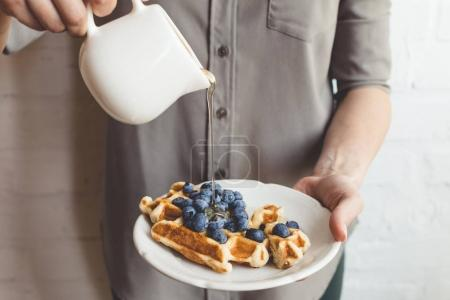 woman pouring syrup on tasty waffles