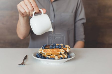 Photo for Cropped shot of woman pouring sweet syrup on tasty waffles - Royalty Free Image