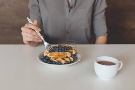 Photo for Cropped shot of woman eating waffles with blueberries for breakfast - Royalty Free Image