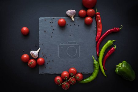 Photo for Top view of fresh ripe tomatoes, peppers and garlic with blank slate board - Royalty Free Image