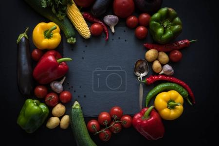 Photo for Top view of various fresh ripe vegetables and spoon on slate board - Royalty Free Image