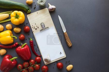 Photo for Top view of various fresh ripe vegetables with blank clipboard, cutting board and knife on grey - Royalty Free Image
