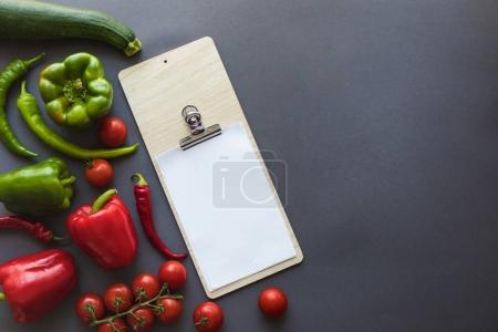 vegetables with blank paper and cutting board