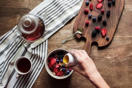 Photo pour Vue du dessus des flocons de thé et de maïs avec des baies sur une table en bois - image libre de droit
