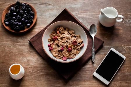 corn flakes, berries and smartphone