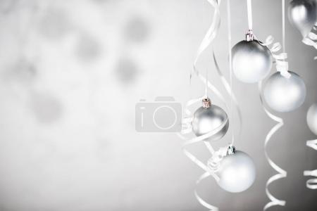 Foto de Cerrar vista de brillantes juguetes de Navidad en cintas aisladas en gris - Imagen libre de derechos