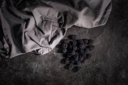 Photo pour Vue de dessus des mûres fraîches saines et du tissu sur la surface noire - image libre de droit