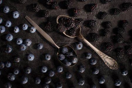 Photo pour Vue de dessus de cuillères vintage avec les bleuets et les mûres mûres fraîches sur fond noir - image libre de droit