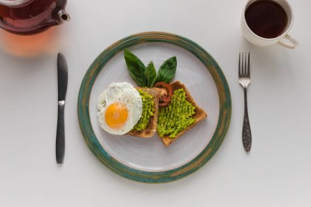 Photo pour Vue de dessus de l'oeuf frit et de l'avocat écrasé sur les toasts pour le petit déjeuner, isolé sur blanc - image libre de droit