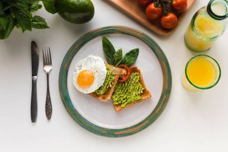 Photo for Top view of fried egg and mashed avocado on toasts for breakfast with orange juice, isolated on white - Royalty Free Image