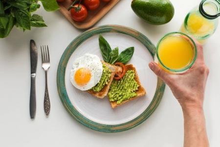 Photo pour Vue recadrée de la personne qui mange des œufs frits et de la purée d'avocat sur des toasts pour le petit déjeuner avec du jus d'orange, isolé sur du blanc - image libre de droit