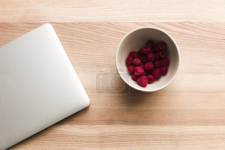 Laptop and bowl with raspberries
